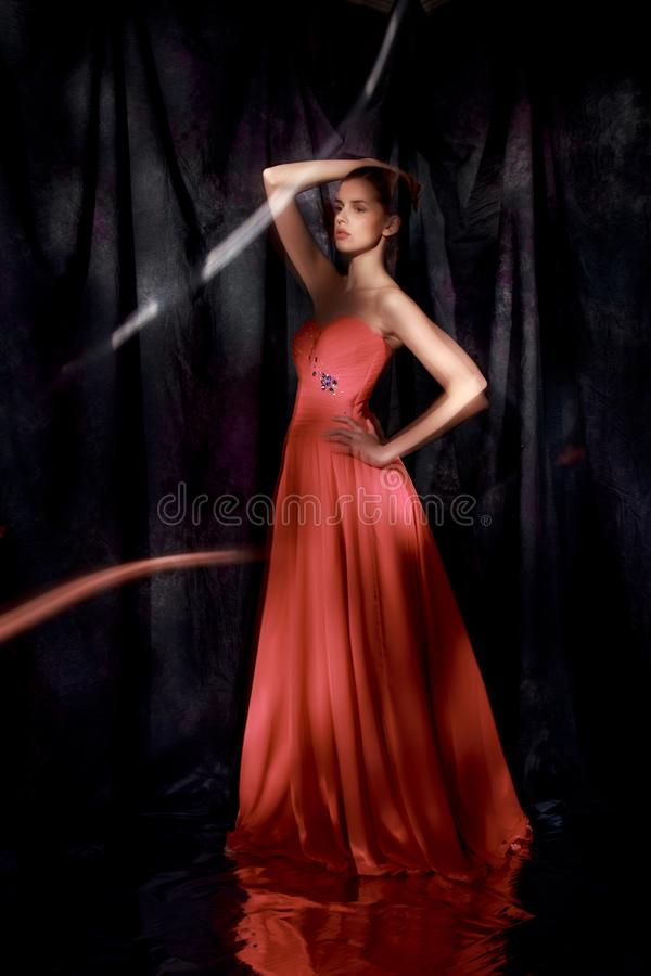 红色晚礼服的美丽的妇女在黑暗的背景 免版税库存照片