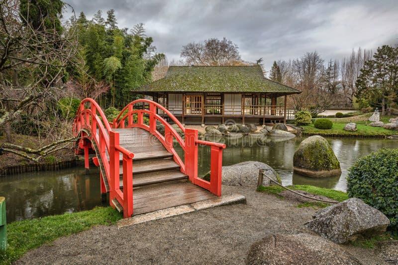 红色曲拱桥梁在公开日本庭院里在图卢兹 图库摄影