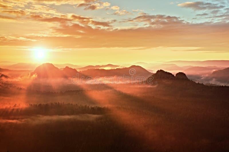 红色有薄雾的破晓 在的有雾的秋天早晨美丽的小山 小山峰顶从富有的五颜六色的云彩非常突出  免版税库存照片