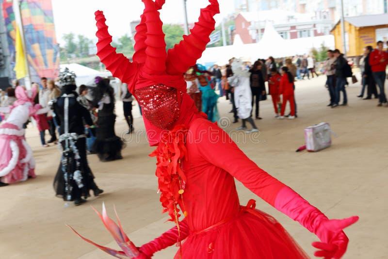 红色服装的舞蹈家在街道剧院在露天节日不眠夜里摆在显示 免版税库存图片