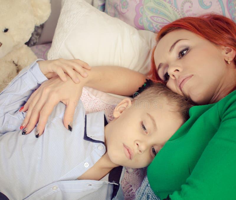 红色朝向的母亲和儿子在床上 库存图片