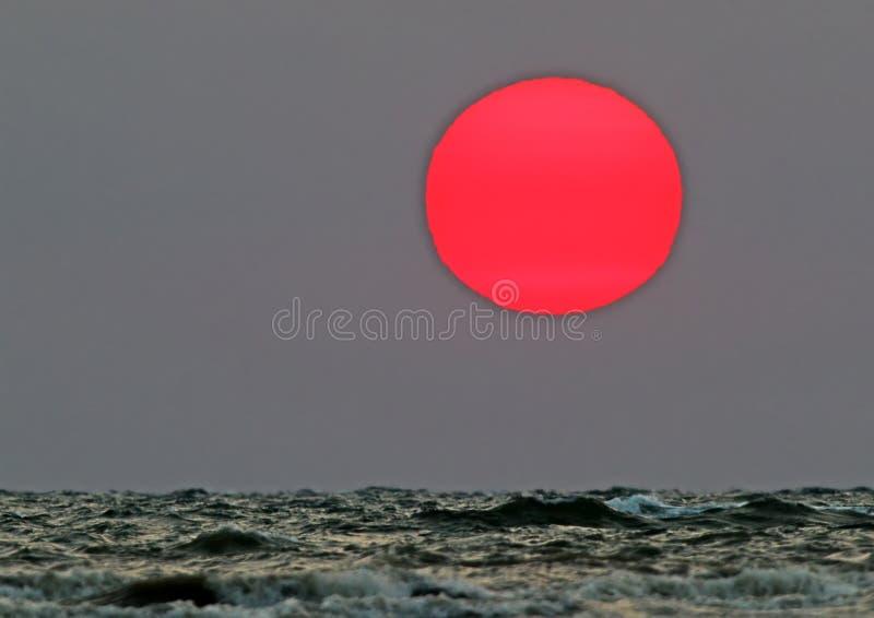 红色朝阳的原始的射击在阴沉的海的 库存照片