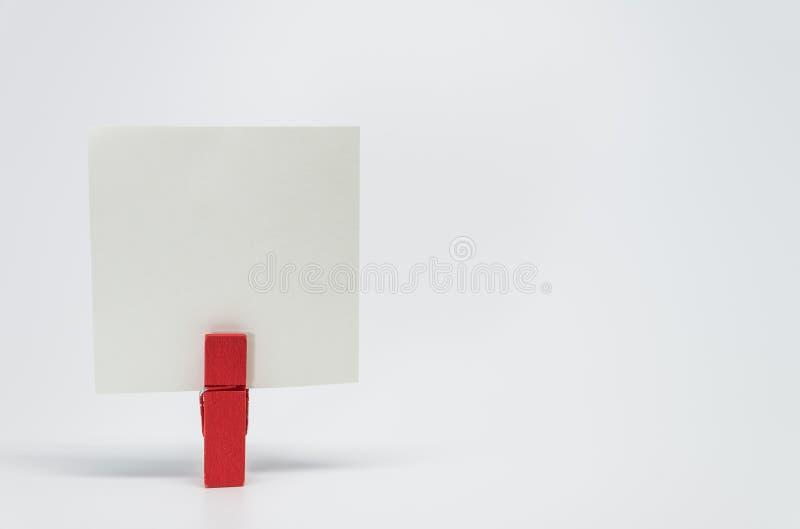 红色木夹子夹紧的备忘录纸张有白色背景和选择聚焦 库存照片