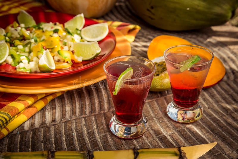 红色杯在泰国样式的水果鸡尾酒用橙色椰子 免版税图库摄影