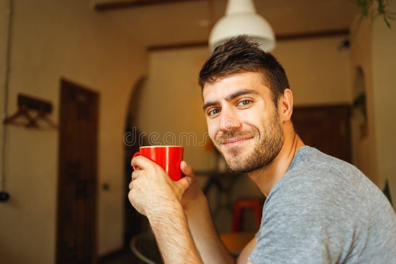红色杯子在微笑的手上英俊 库存图片