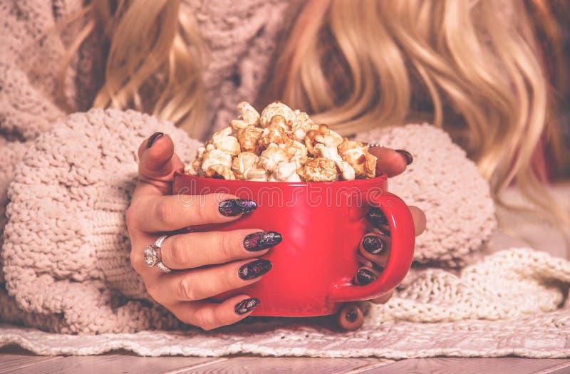 红色杯子开胃金黄玉米花在女性手上 女性手和杯子玉米花 免版税图库摄影