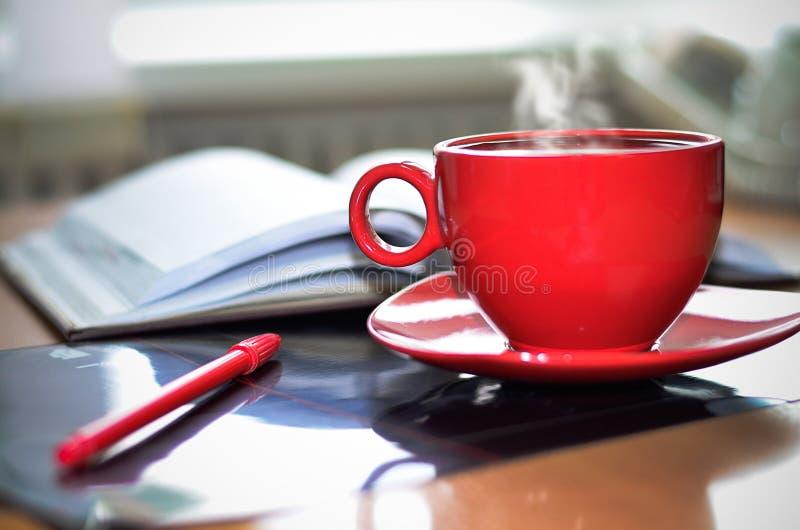 红色杯子热的咖啡、笔记薄和铅笔在桌面上在办公室 免版税图库摄影
