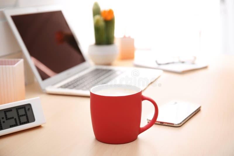 红色杯子用咖啡和电话在膝上型计算机附近 图库摄影