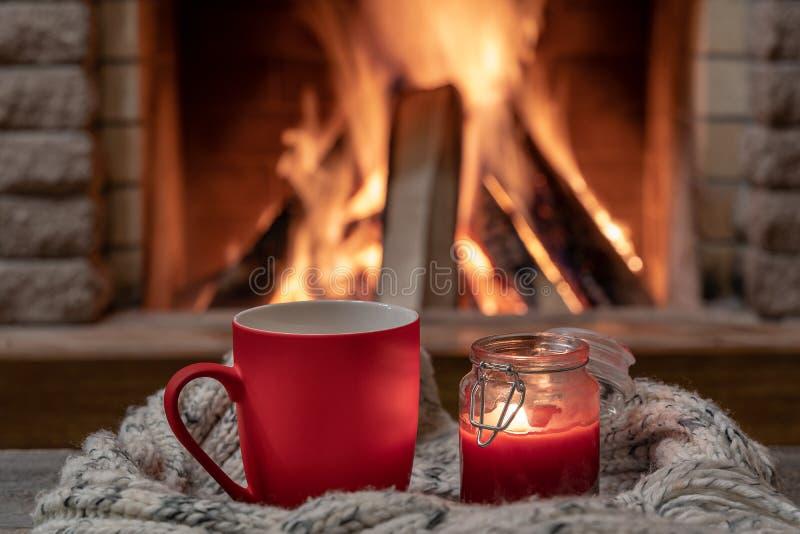 红色杯子用热的茶和一个蜡烛,羊毛围巾,在舒适壁炉附近,hygge,家甜家 免版税库存照片