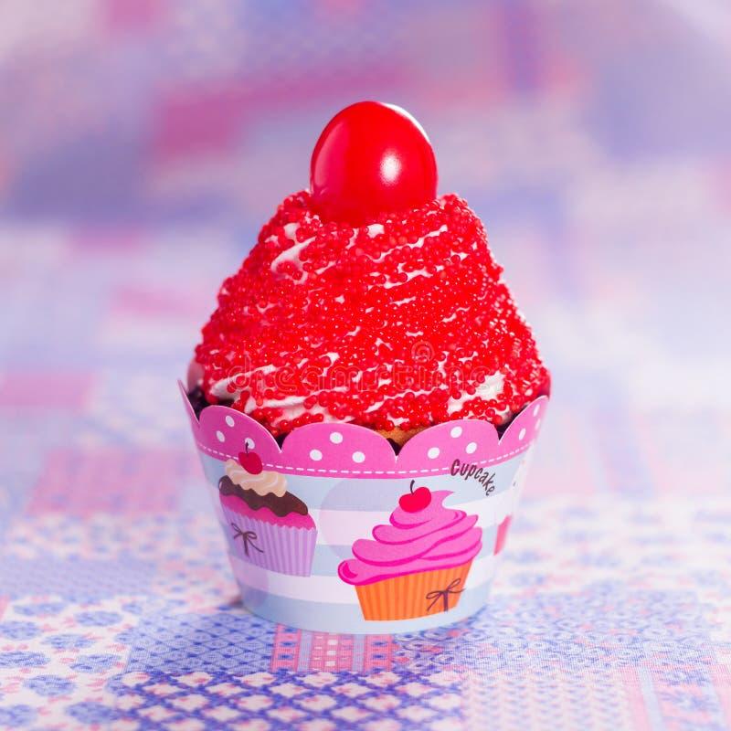 红色杯形蛋糕用在上面和紫色背景的樱桃 库存照片