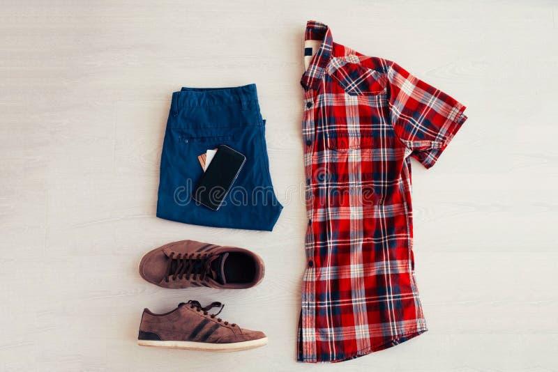 红色格子衬衫、牛仔裤短裤和白色运动鞋在白色背景,人是衣裳 免版税图库摄影