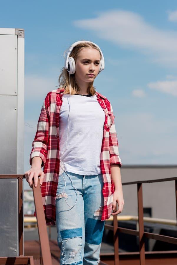 红色格子衬衫和耳机的美丽的青少年的女孩在前面 免版税库存照片