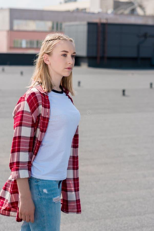 红色格子衬衫的时髦的青少年的女孩 免版税库存图片