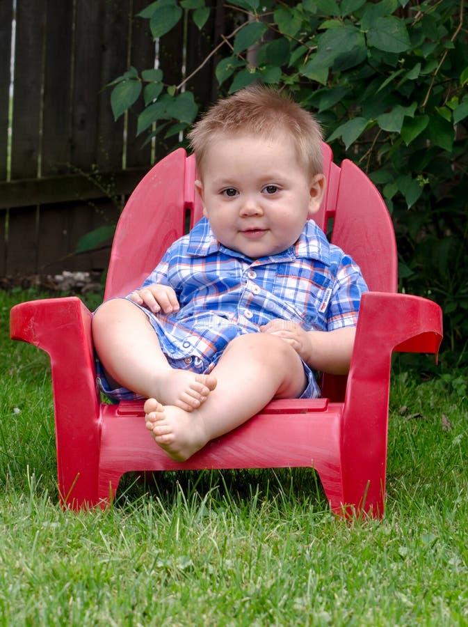 红色椅子的年轻小孩 库存照片