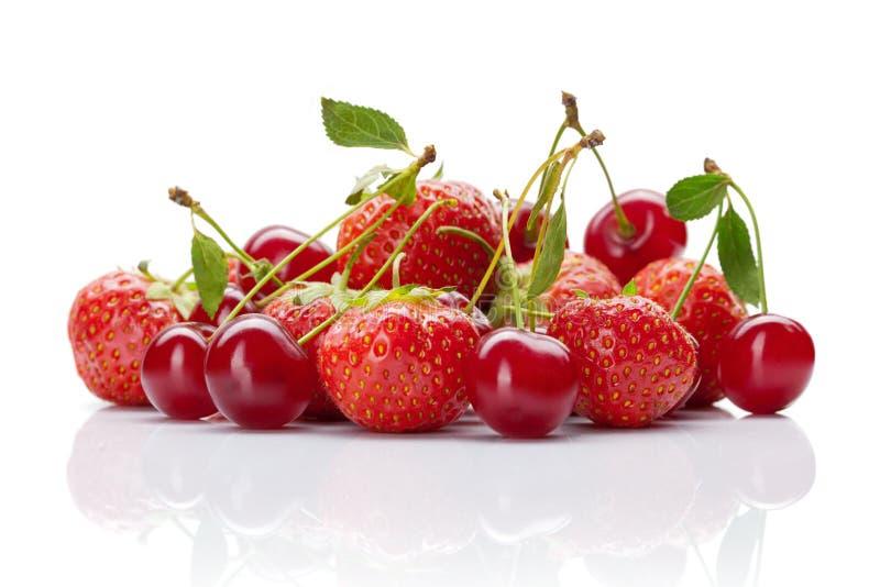 红色樱桃用在白色的草莓 免版税库存图片