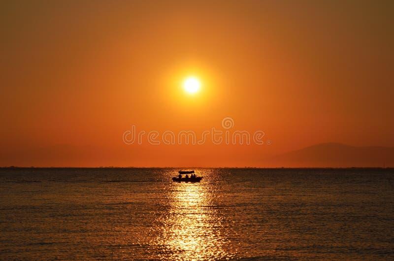 红色橙色太阳和小船的剪影 图库摄影