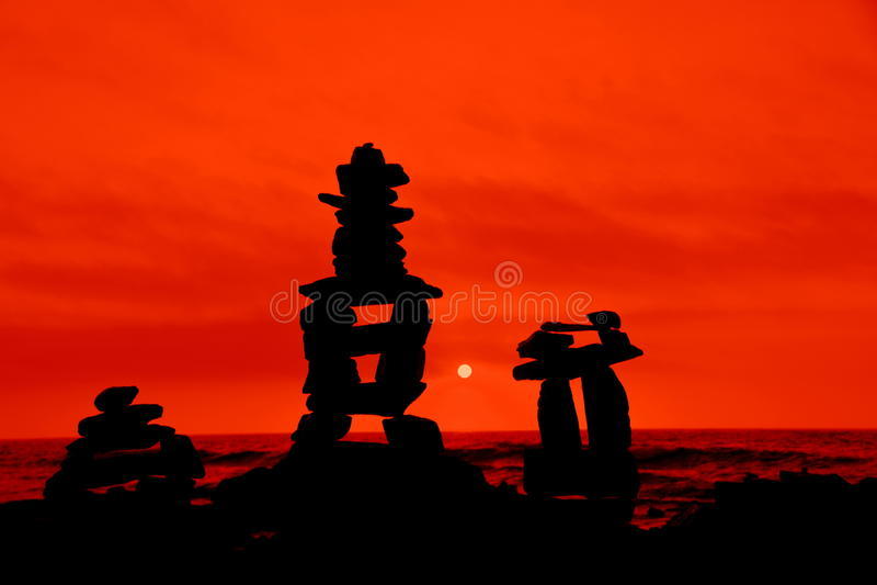 红色橙色背景现出轮廓的岩石石标 免版税库存照片