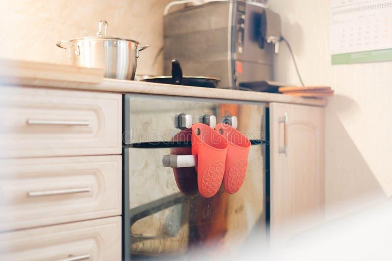 红色橡胶厨房手套 在电磁炉的吊 它也有一个平底锅和一个煎锅 在背景的咖啡机, 库存图片