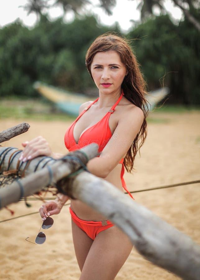 红色比基尼泳装的少妇,斜眼看她的眼睛在明亮的天期间 免版税库存图片