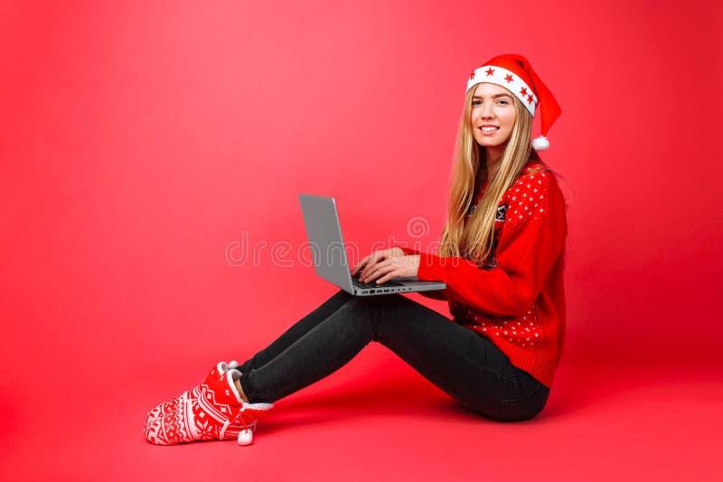 红色毛线衣和圣诞老人帽子坐的企业女孩与在红色背景的膝上型计算机一起使用 免版税库存照片