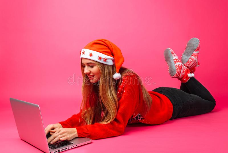 红色毛线衣和圣诞老人帽子坐的工作的企业女孩与 免版税库存照片