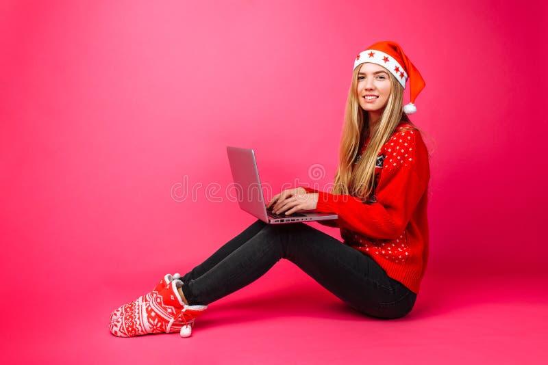红色毛线衣和圣诞老人帽子坐的工作的企业女孩与 图库摄影