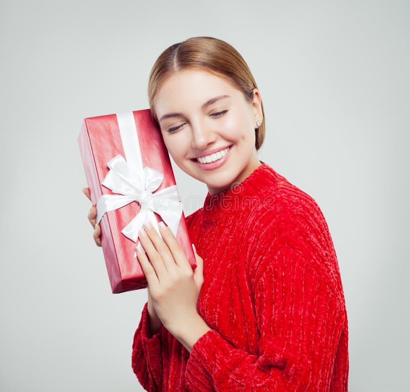 红色毛线衣藏品礼物盒和有乐趣的快乐的妇女 免版税图库摄影