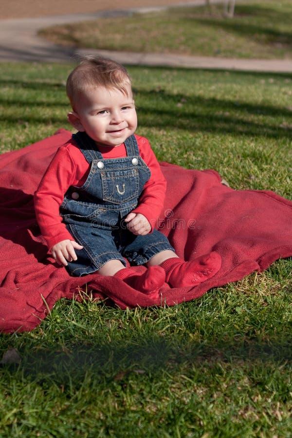 红色毯子的六个月的男孩在草 免版税库存照片
