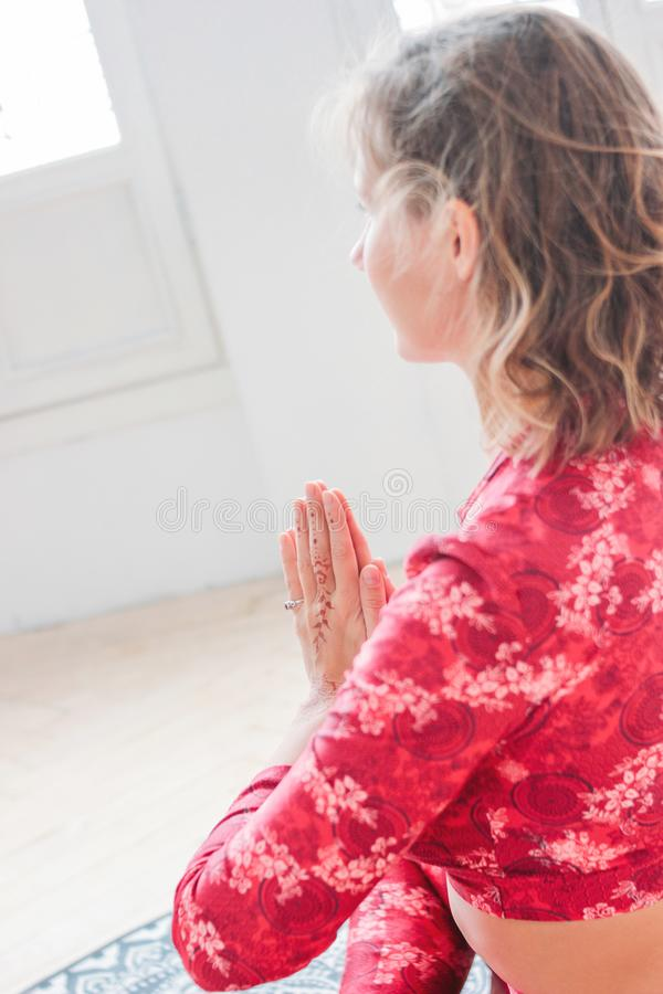 红色民族服装实践的瑜伽asana的Namaste年轻白肤金发的妇女在轻的演播室 库存照片