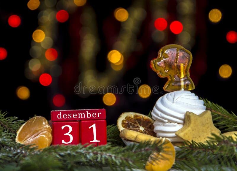 红色求甜点历日12月31日,板材用蛋白软糖和焦糖的立方当黄色和红色bokeh光狗背景  库存图片