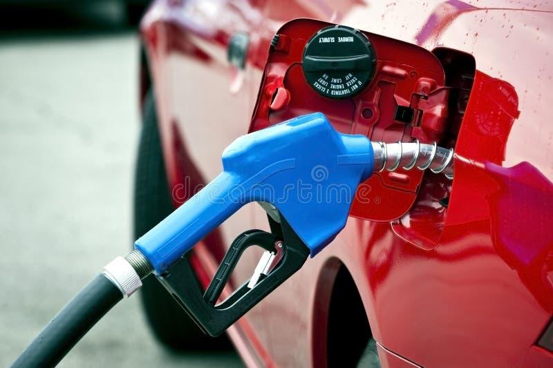 给红色汽车加油的蓝色气管 免版税库存照片