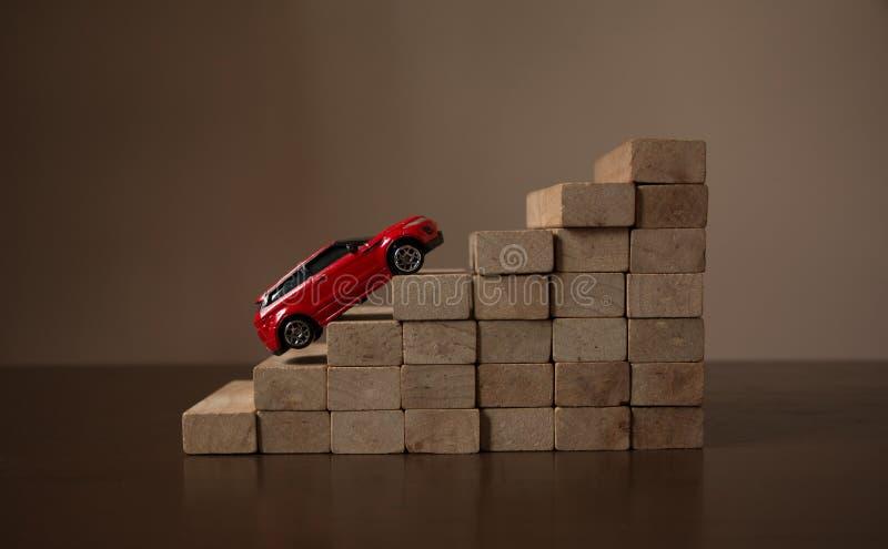 红色汽车在卷台阶步木楼梯堆,自然明亮的轻的背景 免版税库存照片