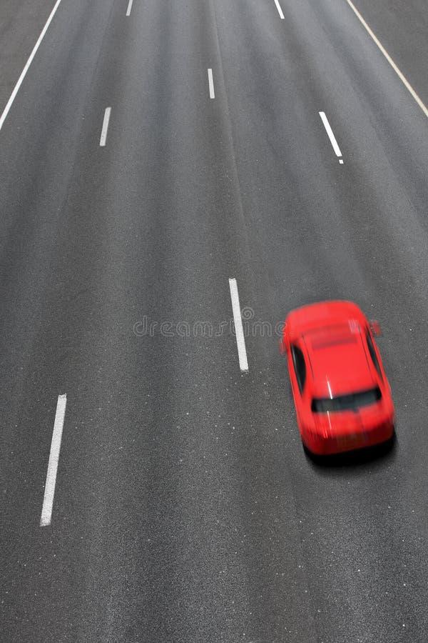 红色汽车在高速公路快速地移动。 库存图片
