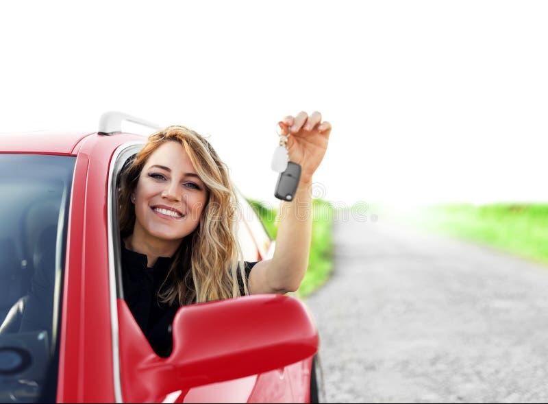 红色汽车的一名可爱的妇女在她的手上把握一个汽车关键 免版税图库摄影
