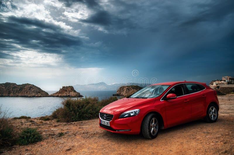 红色汽车站立在峭壁边缘的富豪集团v40反对风雨如磐的天空 免版税库存图片