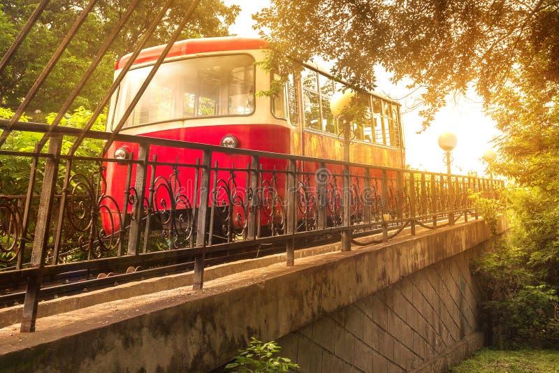 红色汽车缆索铁路在平衡的日落的明亮的阳光下上升在俄国远东的首都 免版税库存图片