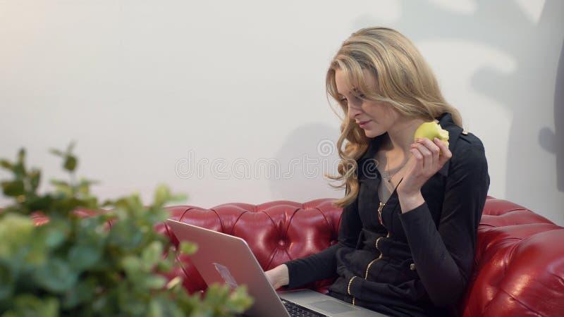 红色沙发的美丽的年轻白肤金发的妇女使用膝上型计算机和吃一个绿色苹果在客厅 免版税库存图片