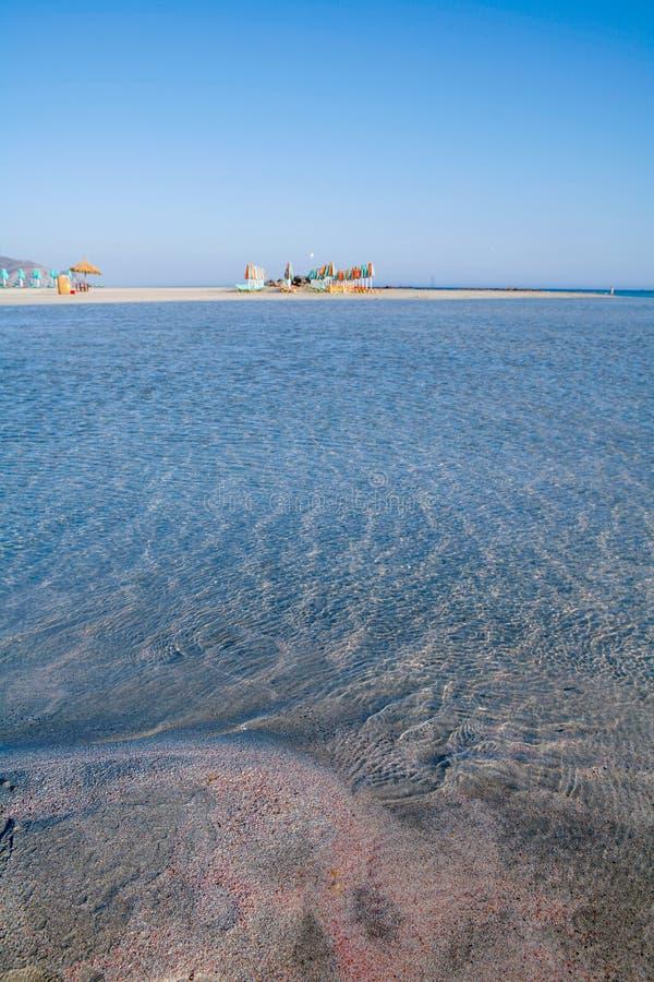 红色沙子明白海和沙滩伞 免版税库存图片