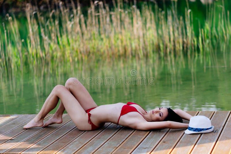 红色游泳衣的秀丽妇女晒日光浴在湖码头的 免版税图库摄影