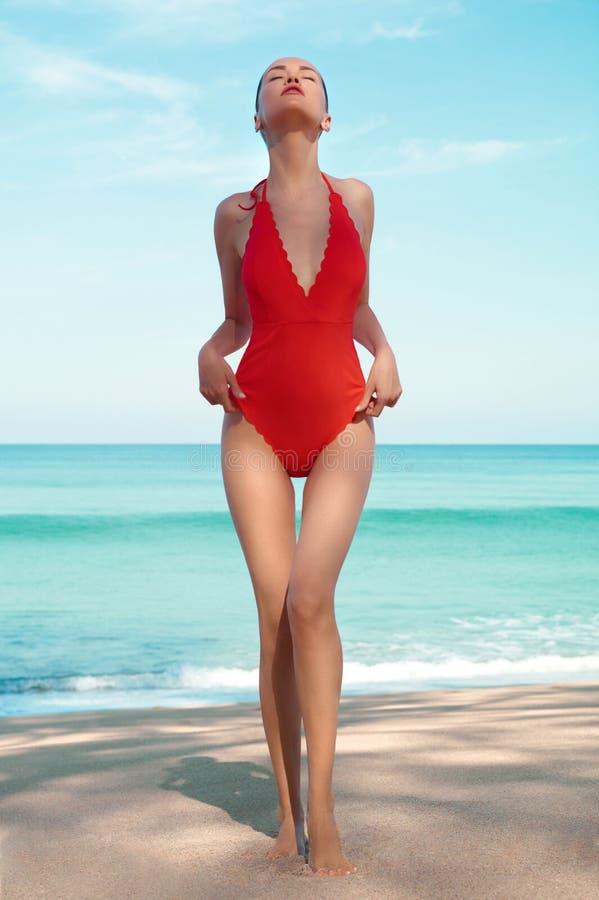 红色游泳衣的美丽的性感的妇女在海滩 库存图片