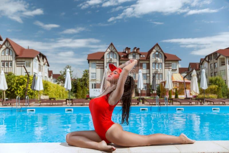 红色游泳衣的美女在水池附近的一家美丽的旅馆里 库存图片