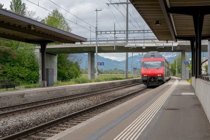 红色火车速度通过与没人的一个小农村火车站平台的 图库摄影