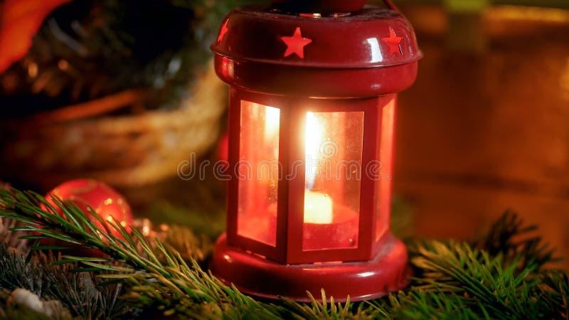 红色灯笼的特写镜头图象有烧的小蜡烛在客厅的木桌上自圣诞前夕 免版税库存照片