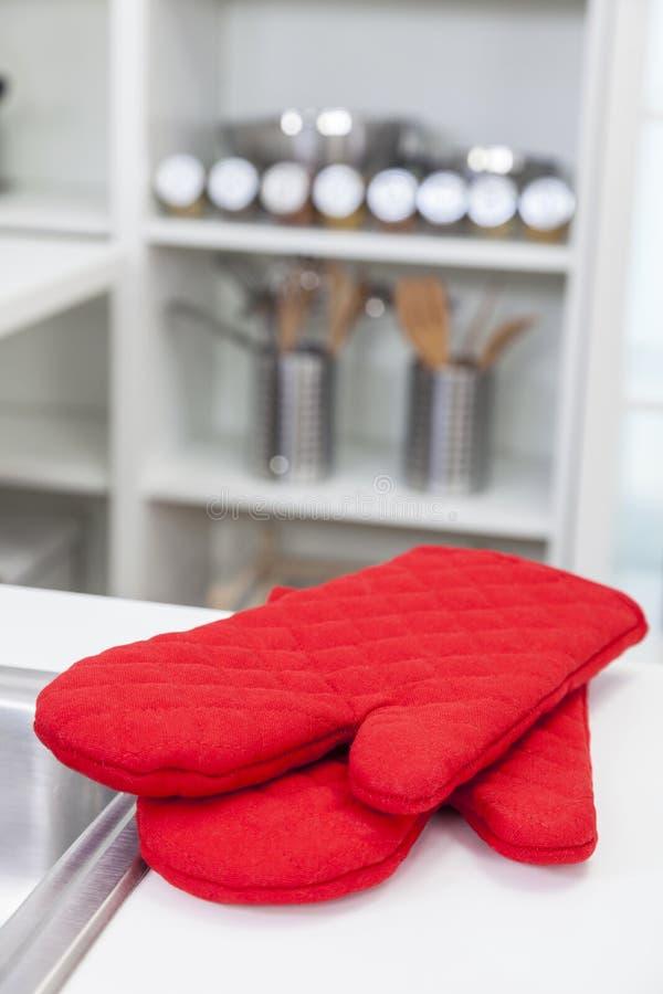 红色烤箱手套手套在一个现代厨房里 库存照片