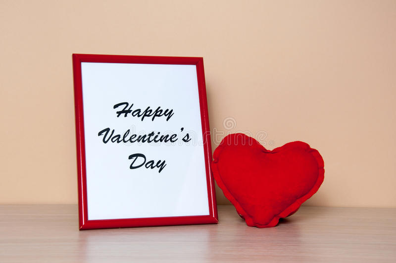 红色照片框架和心脏在木桌上 库存图片