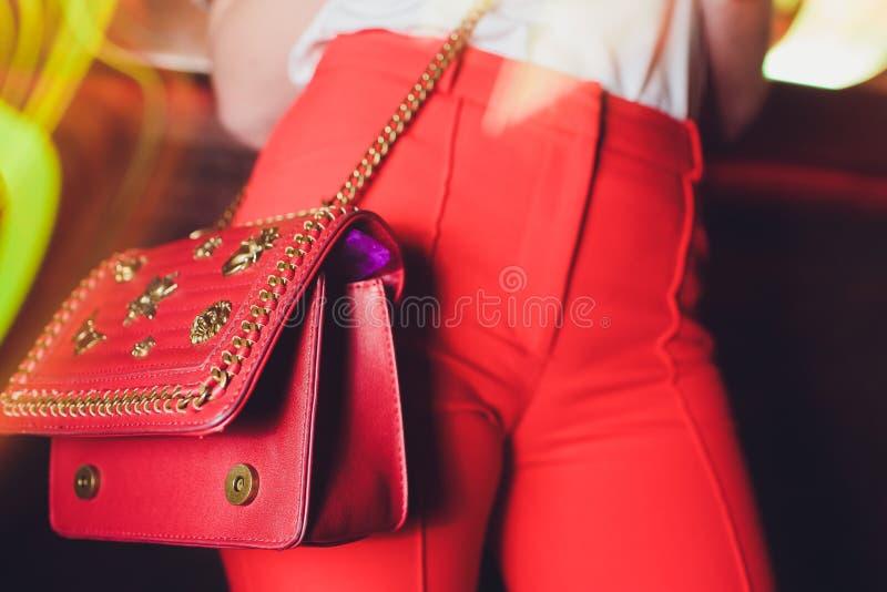 红色牛仔裤和毛线衣的时尚年轻女人有红色袋子传动器的在手上在街道墙壁特写镜头附近 免版税图库摄影