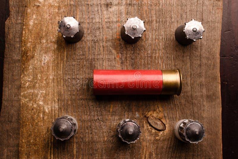 红色狩猎壳和一些枚子弹在一张木桌上说谎 免版税库存照片