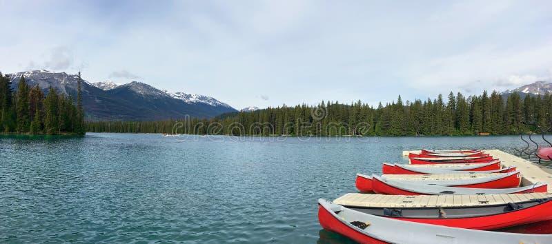 红色独木舟全景在干净的蓝色湖的 免版税库存照片