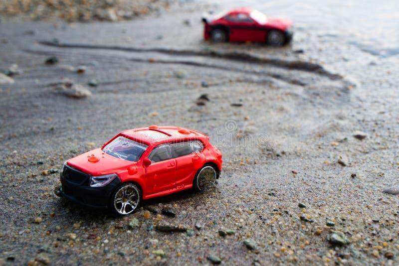 红色玩具不是在海滩的一辆真正的汽车在湿沙子,在被弄脏别的背景中 免版税图库摄影