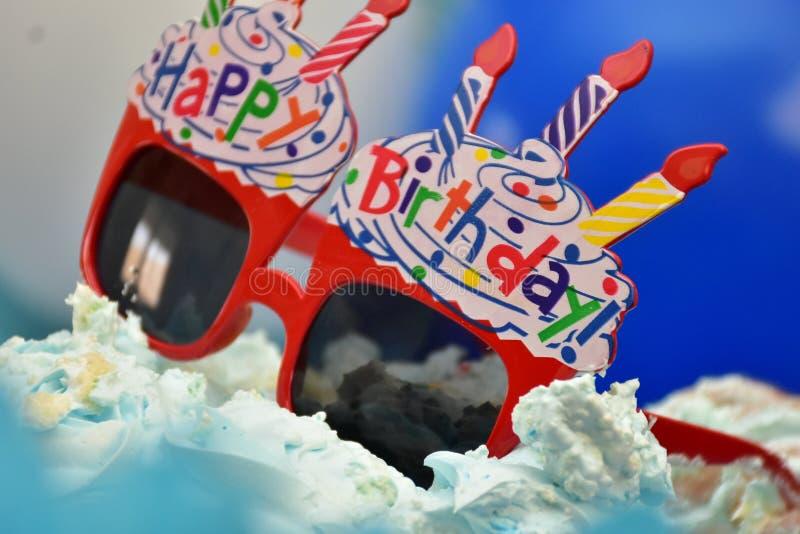 红色玩具与生日快乐蜡烛的太阳镜 库存图片